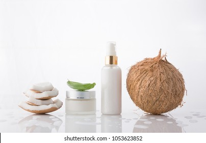 High key homemade cosmetic coconut products with coconut on white background. Lotion cream with coconut stack and green leaf. Droplet reflection.