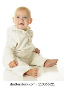 High key image of an adorable baby boy dressed in white.  On a white background.