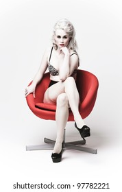 high key image of an attractive young blonde woman in lingerie, posing in a red chair