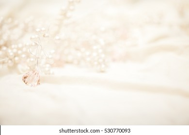 High key image of pearl covered branches and pink crystals on light fabric with shallow depth of field.