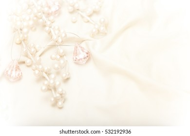 High key image of pearl covered branches and pink crystals on light fabric shot from above.