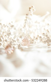 High key image of pearl covered branches and pink branches on light fabric with shallow depth of field.