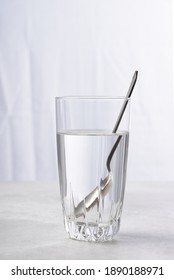 High key image of a teaspoon in glass of water with refraction.