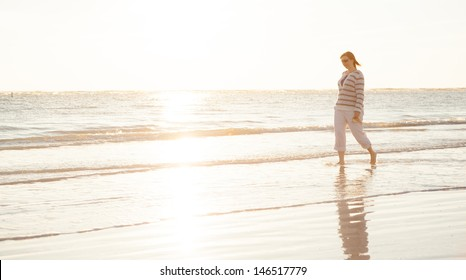 High Key Image of Woman Walking in the Ocean Waves at the Beach