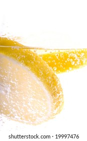 High Key macro image of lemon slices floating in bubbly mineral water.
