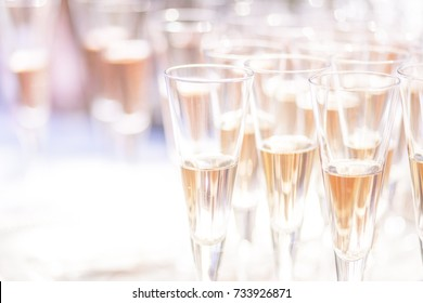 high key, overexposed image of champagne flutes with sparkling pink wine.