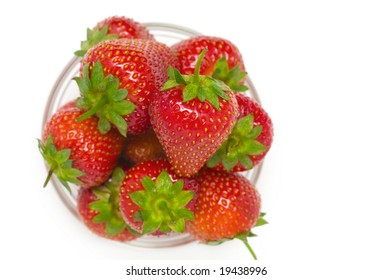 High key photo of fruit dish filled with nice red strawberries