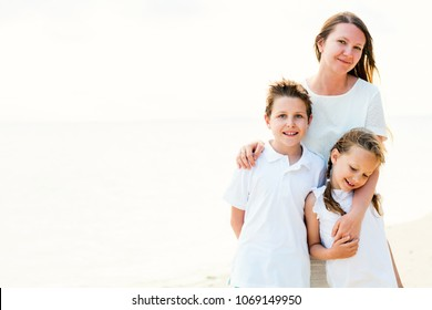 High key photo of happy beautiful family with kids on a tropical beach vacation