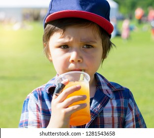 High key Portrait of kid boy drinking orange slush from plastic glass in hot sunny day,Thirsty child drinking frozen orange slush while waking at the park, Summer drink for the kids