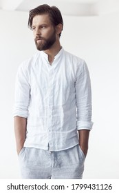 high key portrait photo on white cyclorama of a handsome bearded man with brown hair and eyes, he is wearing a white linen shirt and pants, looking away and holding his hands in pockets