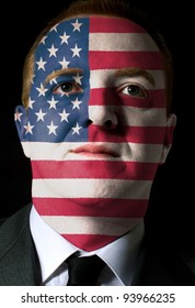 High key portrait of a serious businessman or politician whose face is painted in national colors of american flag