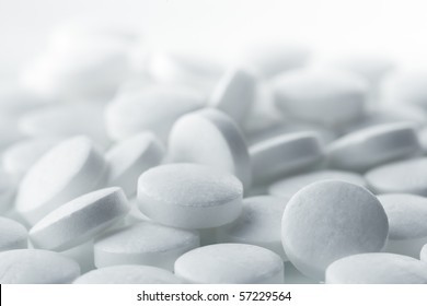 High key shot of white pills brightly lit.