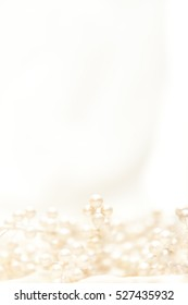 High key vertical image of pearl covered branches on light fabric with shallow depth of field.