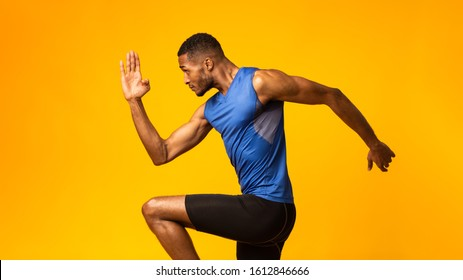 High Knees. Close up of muscular black man doing fitness exercise, lifting leg and waving arm, free space, panorama