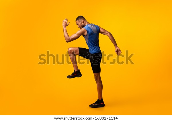 High Knees. Energetic afro man doing fitness exercise, lifting leg and waving arm, free space