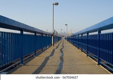 High lamps lined by blue railing and blue sky in background