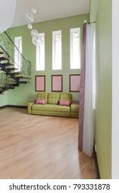 High light interior with green sofa and light parquet