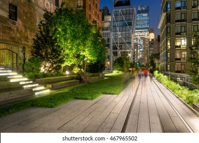 The High Line promenade illuminated at twilight surrounded by modern and older buildings in Chelsea. The aerial green-way is also known as Highline or High Line Park. Manhattan, New York CIty