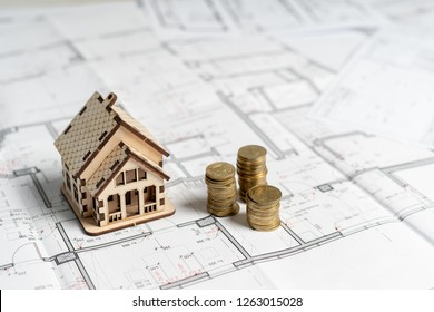 High and low flat or apartment price concept. How much does it cost? High angle above top view small miniature wooden house stand inside bright workstation on table near stack of gold coins