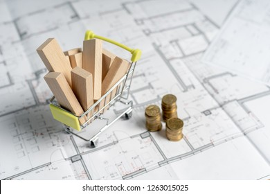 High and low price concept. High angle above top view small miniature object of shopping cart full of sawmill construction materials standing on table with stack of gold coins indoor light room