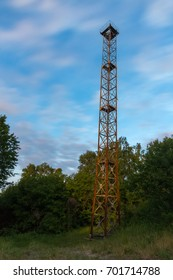 High metal tower in the forest at night.