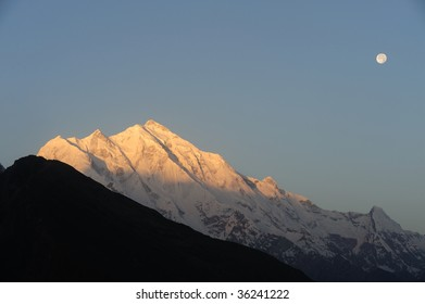 High Mountain and Full Moon in Sunrise