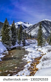 High mountain peaks and trees covered with freshly fallen snow with water flowing in river in alpine valley on sunny afternoon