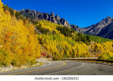 High mountain road twisting through colorful yellow aspen forest with rocky peaks in distance