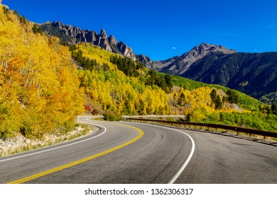 High mountain road twisting through colorful yellow aspen forest with rocky peaks in distance on sunny blue sky afternoon