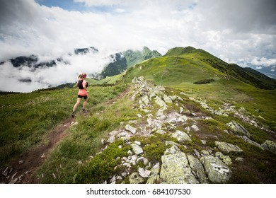 high mountain trail runner female running fast in the summer time with beautiful and epic peak view