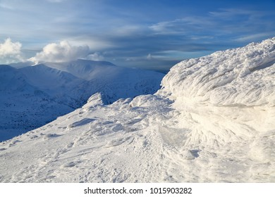 High mountains and blue sky. Mysterious fantastic rocks frozen with ice and snow of strange fairytales forms and structures. Cryptic landscape. Carpathian national park, Chornohirskiy ridge, Ukraine.