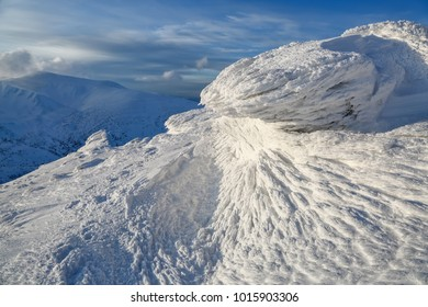 High mountains and blue sky. Mysterious fantastic rocks frozen with ice and snow of strange fairytales forms and structures. Cryptic landscape. Carpathian national park, Chornohirskiy ridge.