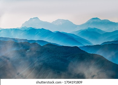 High mountains with green slopes in dense fog. Layers of mountains in the haze during sunset. Multilayered misty mountains. Krasnaya Polyana, Sochi, Russia.