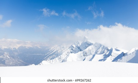 High mountains, lots of white pure snow and clouds lie on the mountains in Sochi, Russia
