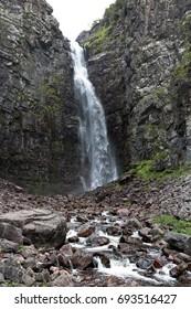 High, narrow waterfall over slate stones.