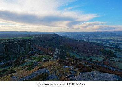 High on Curbar Edge in the Derbyshire Peak District the morning autumnal sun begins to light up the landscape