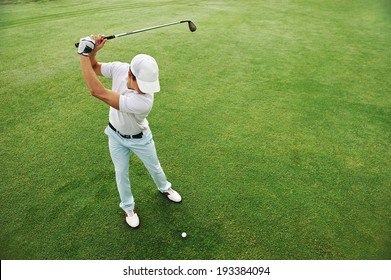 High overhead angle view of golfer hitting golf ball on fairway green grass