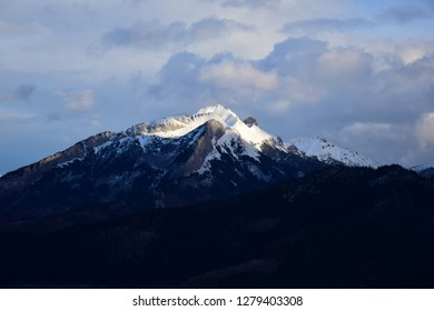 High peak in the center of the landscape. Mountain view in the winter season. Clouds and snow above the top of the mountain. Tatra mountains scenery.