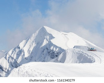 High peaks, lots of white snow in the mountains and clouds cling to the peak in the mountains of Sochi and the ski slope, Russia