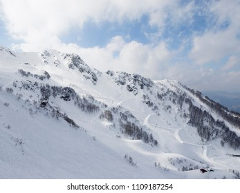 High peaks, a lot of white snow in the mountains and clouds in the mountains of Sochi and the ski slope, Russia