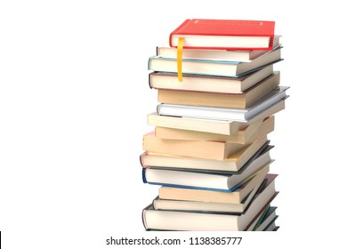 High pile of different books isolated on a white background. Red book with yellow bookmark on top of the pile