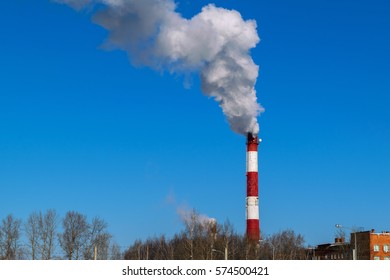 High pipe thermal power plant on the background of blue sky, fog, smog, and out clouds of thick smoke, pipe red-and-white, it's cold outside.