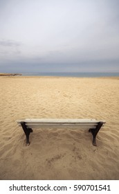 High point of view of an old empty bench on sandy beach at a dull evening.