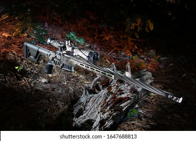 High powered bolt action rifle and riflescope in thick woods