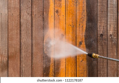 High pressure power washer spraying and cleaning wooden fence. Make old turn new. Dirty fence turned brand new again. Brown dirty grimy wood turned into golden oak again