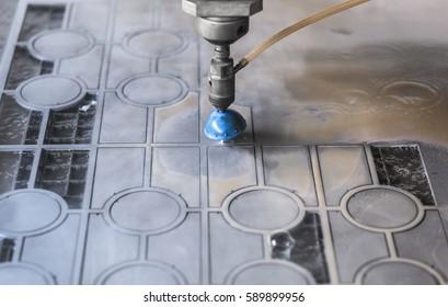 High pressure water jet cutting metal plate.