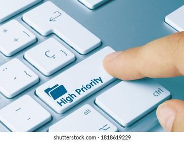 High Priority Written on Blue Key of Metallic Keyboard. Finger pressing key.