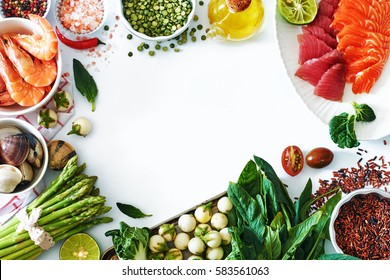 High protein dinner ingredients food frame. Salmon and tuna sashimi, cooked shrimps, clamps, brown rice, asparagus, spinach, olive oil, salt and pepper. White background, copy space.