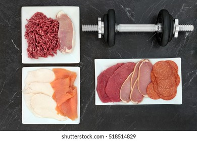 High protein food for body builders with red and white meat and fish on porcelain plates with dumbbell weights.