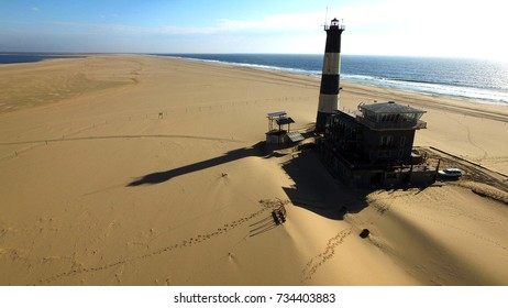 High quality aerial drone photo of desert sand peninsula, old lighthouse, old power station building on seals beach, Walvis Bay lagoon with sea ships at Namibia's Atlantic west coast, southern Africa